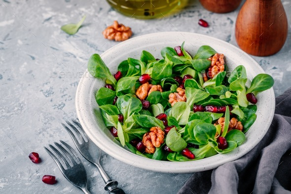Healthy green Lamb's lettuce salad with walnuts and pomegranate seeds - Stock Photo - Images