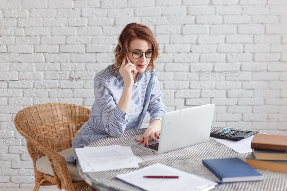Young businesswoman working at the computer and talking on the phone. - Stock Photo - Images