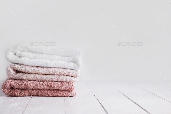 Stack of clean towels on wooden table in bathroom. - Stock Photo - Images