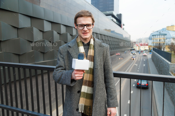 A happy reporter leads a report on the camera on the street - Stock Photo - Images