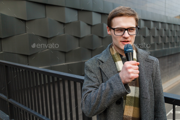 Young news reporter with microphone is broadcasting on the street. Fashion or business news. - Stock Photo - Images