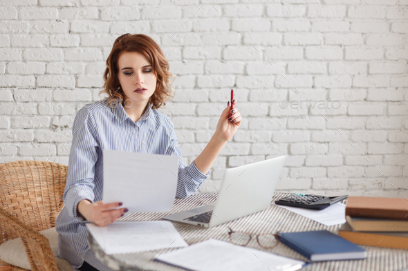 Portrait of a businesswoman working at office reading a document. - Stock Photo - Images