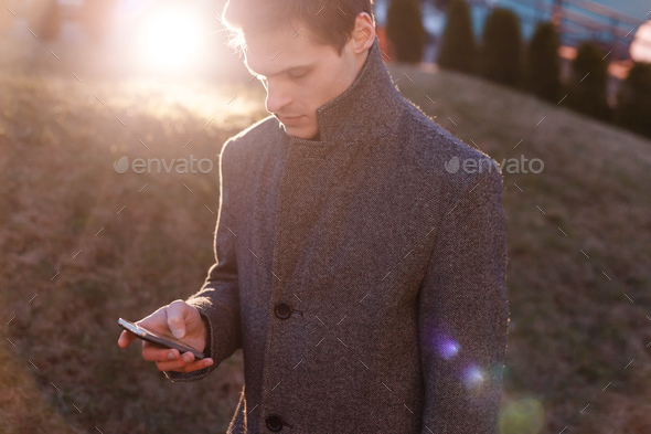 A handsome young businessman using his phone - Stock Photo - Images