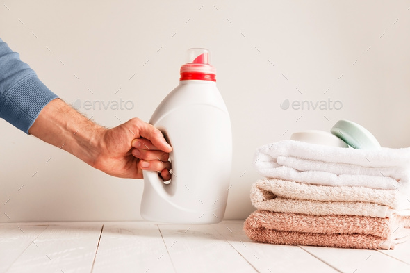 Man's hand putting on the table bottle of detergent gel - Stock Photo - Images