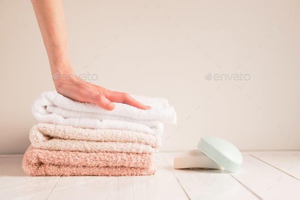 Woman's hand and a stack of soft towels - Stock Photo - Images