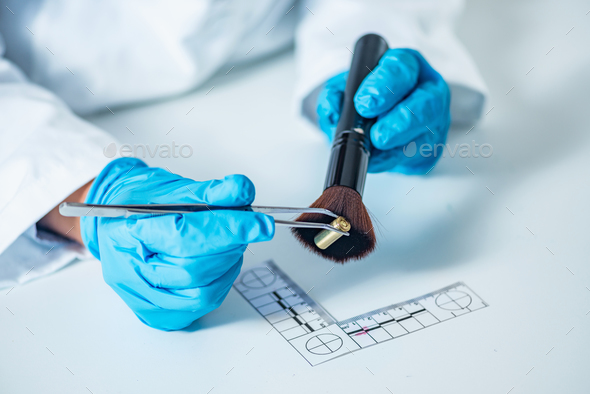 Forensic scientist examining bullet casing - Stock Photo - Images