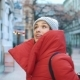 Beautiful Woman in Red Winter Jacket Walks Along the Street Covered with Snow in a Beautiful Old - VideoHive Item for Sale