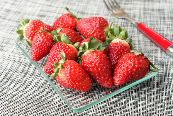 bunch of ripe strawberries in glass tray - Stock Photo - Images