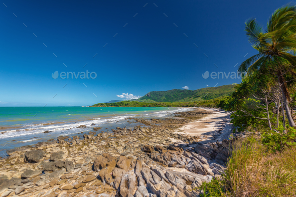 Ellis Beach with rocks near Palm Cove, Queensland, Australia - Stock Photo - Images