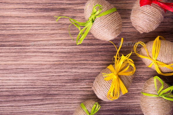 Easter egg in twine near wooden background. - Stock Photo - Images