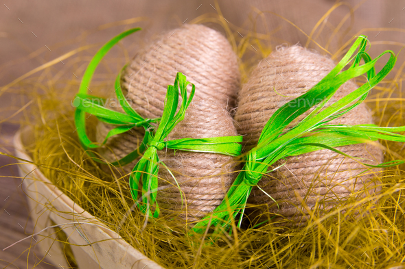 Easter eggs wrapped in twine in yellow nest - Stock Photo - Images