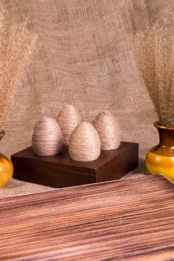 Easter eggs in twine on brown wooden - Stock Photo - Images