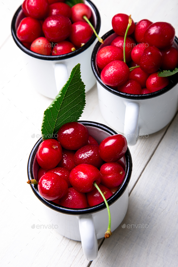 Cherry in enamel cup - Stock Photo - Images