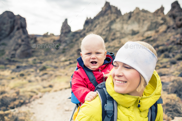 Young mother with little boy travelling in backpack - Stock Photo - Images