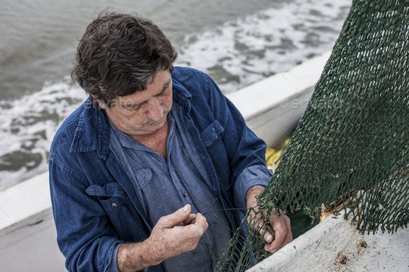 fisherman mending net - Stock Photo - Images