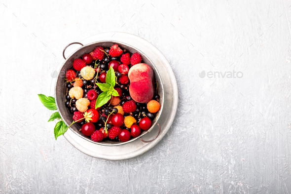 Mix fruit and berries in grey metal bowl - Stock Photo - Images