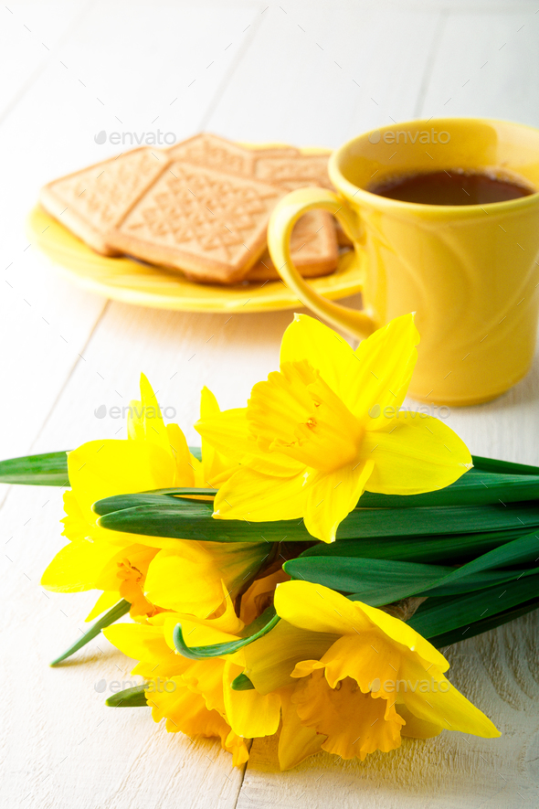 Coffee mug with yellow daffodil flowers - Stock Photo - Images