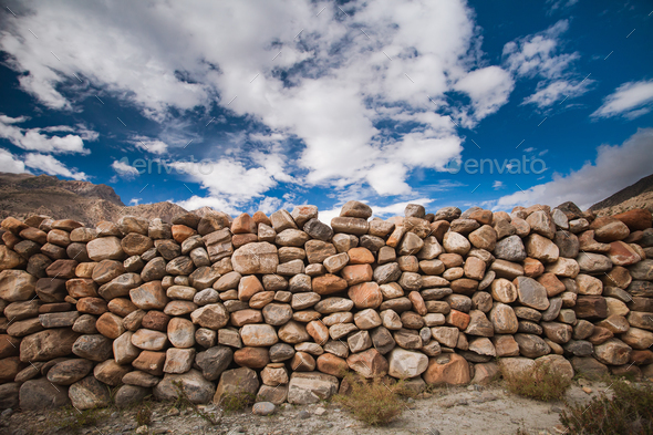 The stone wall under the cloudy sky. Background. - Stock Photo - Images