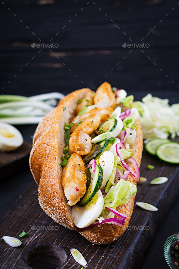 Baguette sandwich with fish, egg, pickled onions and lettuce leaves. - Stock Photo - Images