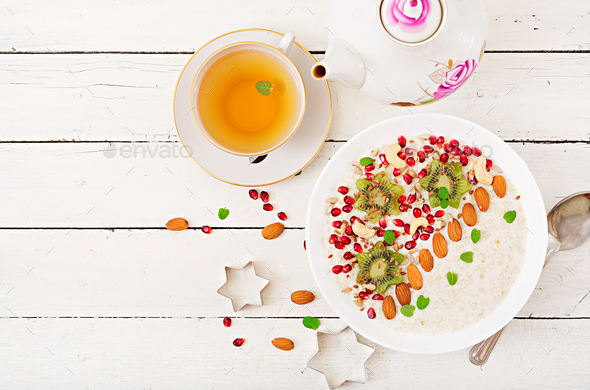 Tasty and healthy oatmeal porridge with kiwi, pomegranate and seeds.  - Stock Photo - Images