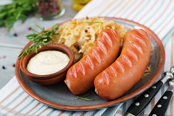 Plate of sausages and sauerkraut on wooden table. Traditional Oktoberfest menu - Stock Photo - Images