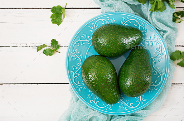 Three ripe avocados on a wooden table. Healthy food concept. Top view - Stock Photo - Images