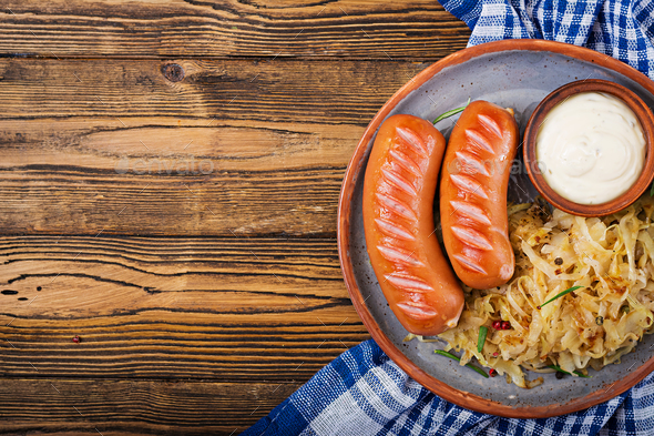 Plate of sausages and sauerkraut on wooden table. Traditional Oktoberfest menu. Flat lay. Top view. - Stock Photo - Images