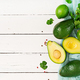 Ripe avocado, lime and cilantro on a light wooden table. Healthy food concept. Top view - PhotoDune Item for Sale