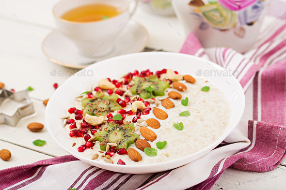 Tasty and healthy oatmeal porridge with kiwi, pomegranate and seeds - Stock Photo - Images