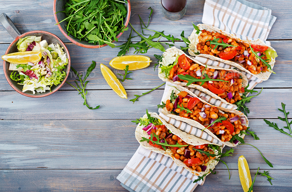 Mexican tacos with beef, beans in tomato sauce and salsa. Flat lay. Top view. - Stock Photo - Images