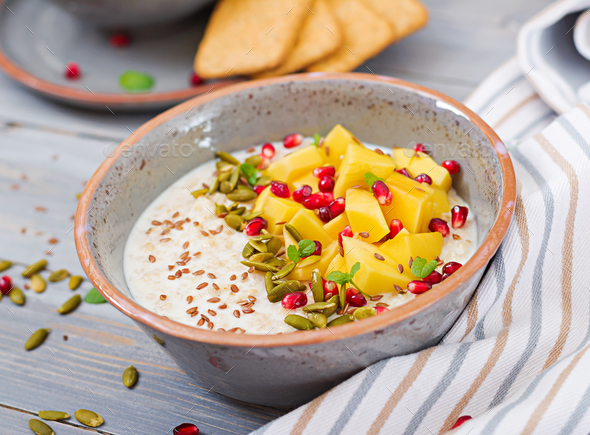 Tasty and healthy oatmeal porridge with mango, pomegranate and seeds - Stock Photo - Images