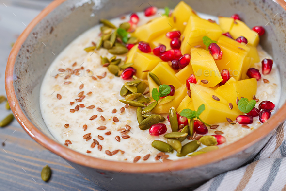 Tasty and healthy oatmeal porridge with mango, pomegranate and seeds. - Stock Photo - Images