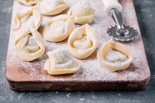 Fresh raw homemade tortellini or ravioli pasta closeup - Stock Photo - Images
