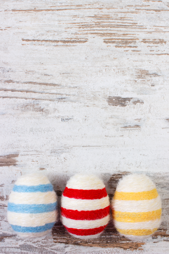 Easter eggs wrapped woolen string on old rustic board, copy space for text, decoration for Easter - Stock Photo - Images