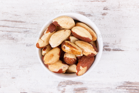 Brazil nuts in glass bowl on rustic board - Stock Photo - Images