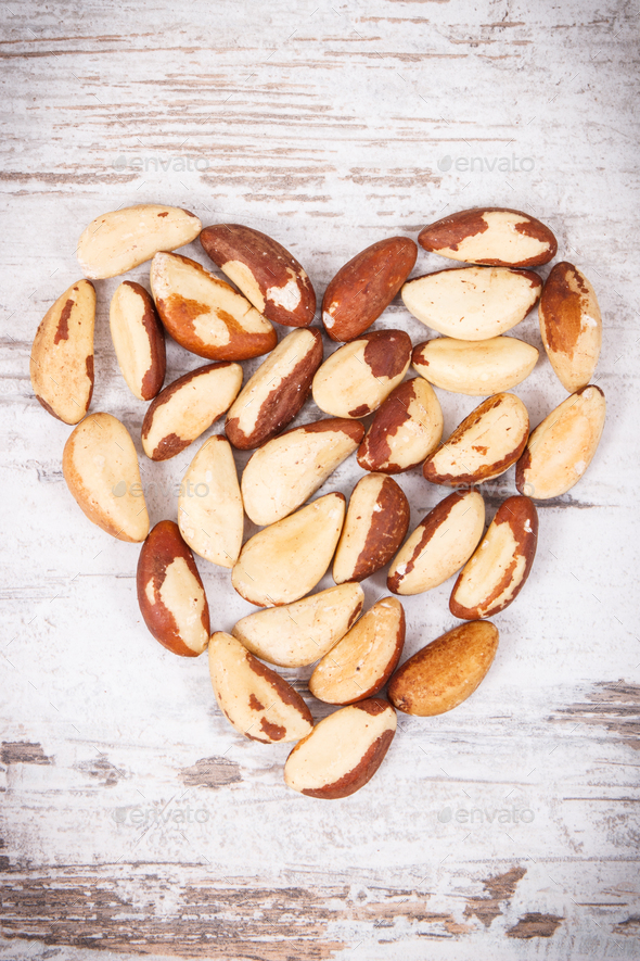 Heap of brazil nuts in shape of heart, healthy food containing natural minerals - Stock Photo - Images