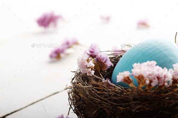 Rustic style painted easter egg in the nest on white table - Stock Photo - Images