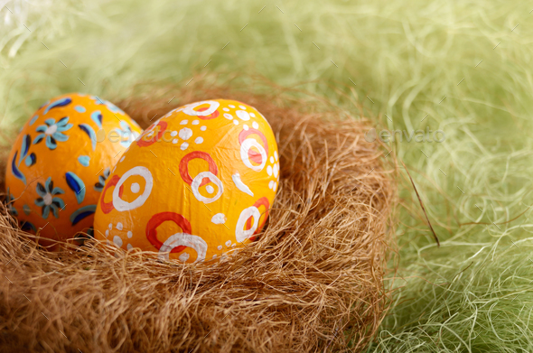 Painted easter eggs in the nest on green background - Stock Photo - Images