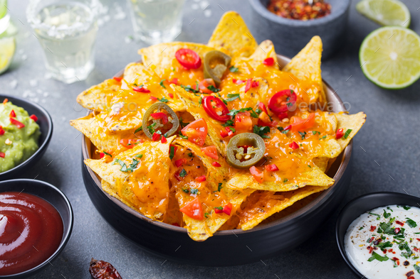 Nachos chips with melted cheese and dips variety. - Stock Photo - Images