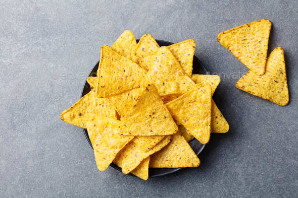 Nachos chips in bowl. Stone background. Top view. - Stock Photo - Images