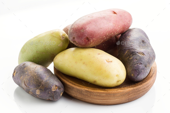 colorful potatoes on wooden board isolated on white - Stock Photo - Images