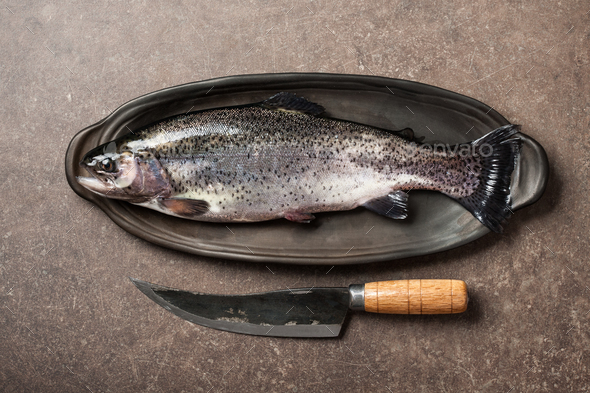 Fresh trout fish and knife on kitchen table - Stock Photo - Images
