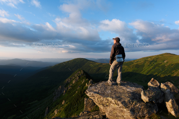 Alone tourist sitting on the edge of the cliff - Stock Photo - Images