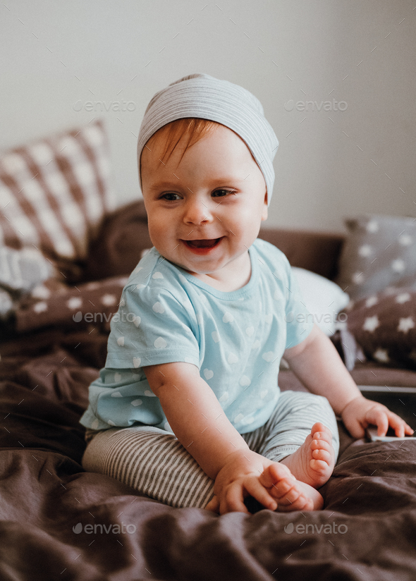 Cute little happy baby girl plays sitting on a bed in a room. Happy family having fun. - Stock Photo - Images