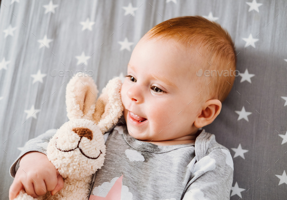 Happy smiling baby girl with her toy on the bed. - Stock Photo - Images