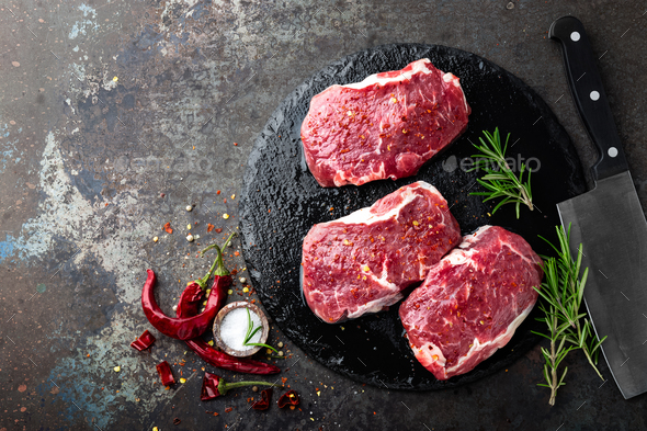 Raw beef meat. Fresh steaks on slate board on black background. Top view - Stock Photo - Images