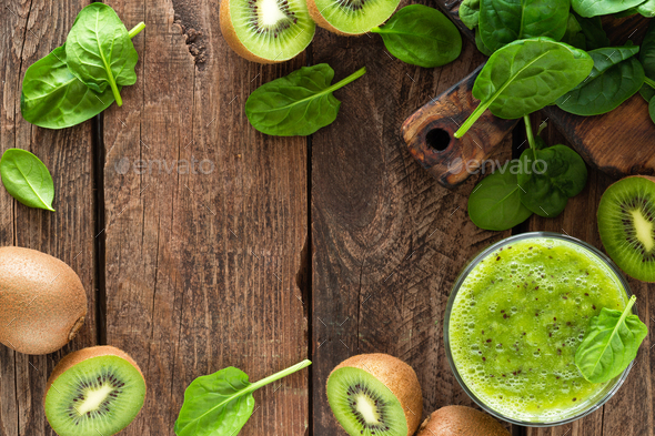 Kiwi smoothie drink of spinach leaves and fresh fruits on wooden rustic table, healthy detox diet - Stock Photo - Images