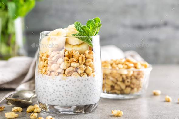 Layered chia pudding parfait with banana, sweet wheat with honey and yogurt, dessert - Stock Photo - Images