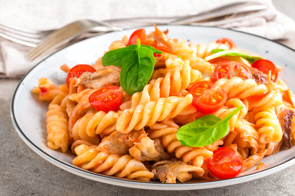Pasta spirali stirred with fried pieces of chicken, cherry tomatoes and tomato sauce - Stock Photo - Images