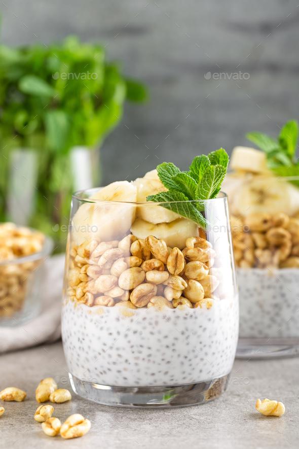 Layered chia pudding parfait with banana, sweet wheat with honey and yogurt, dessert - Stock Photo - Images